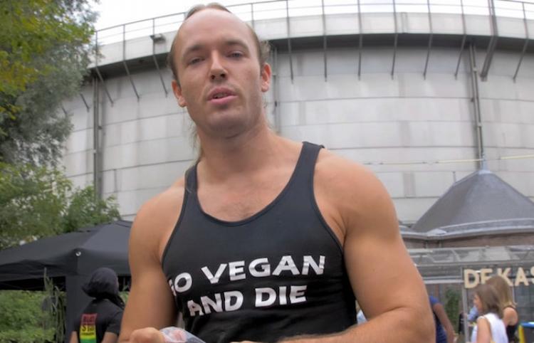 Un hombre come carne cruda en medio de un festival de comida vegana