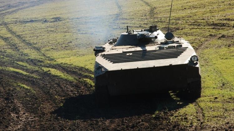 Un vehículo militar blindado aplasta a un coche en una carretera