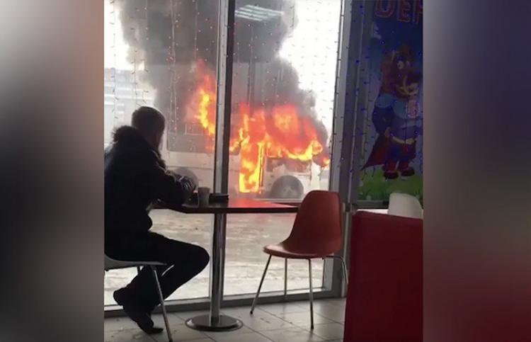 Un joven disfruta de un café a pocos pasos de un autobús en llamas
