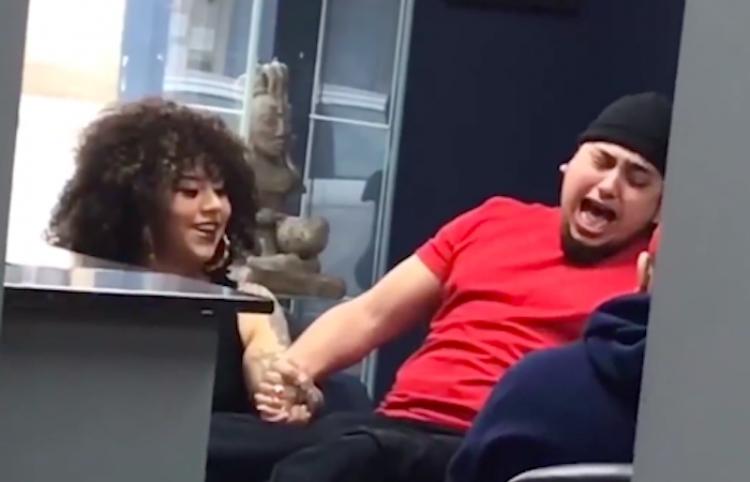 Chica sujeta la mano de su novio mientras sufre por tatuaje